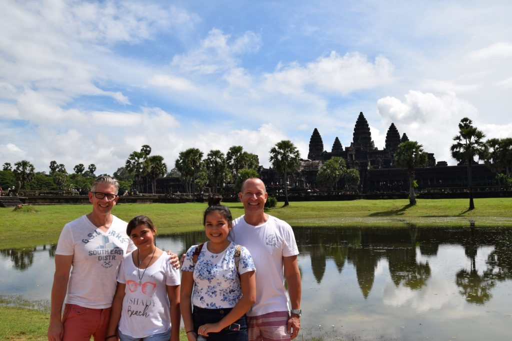 family poses with Angkor Wat in the distance