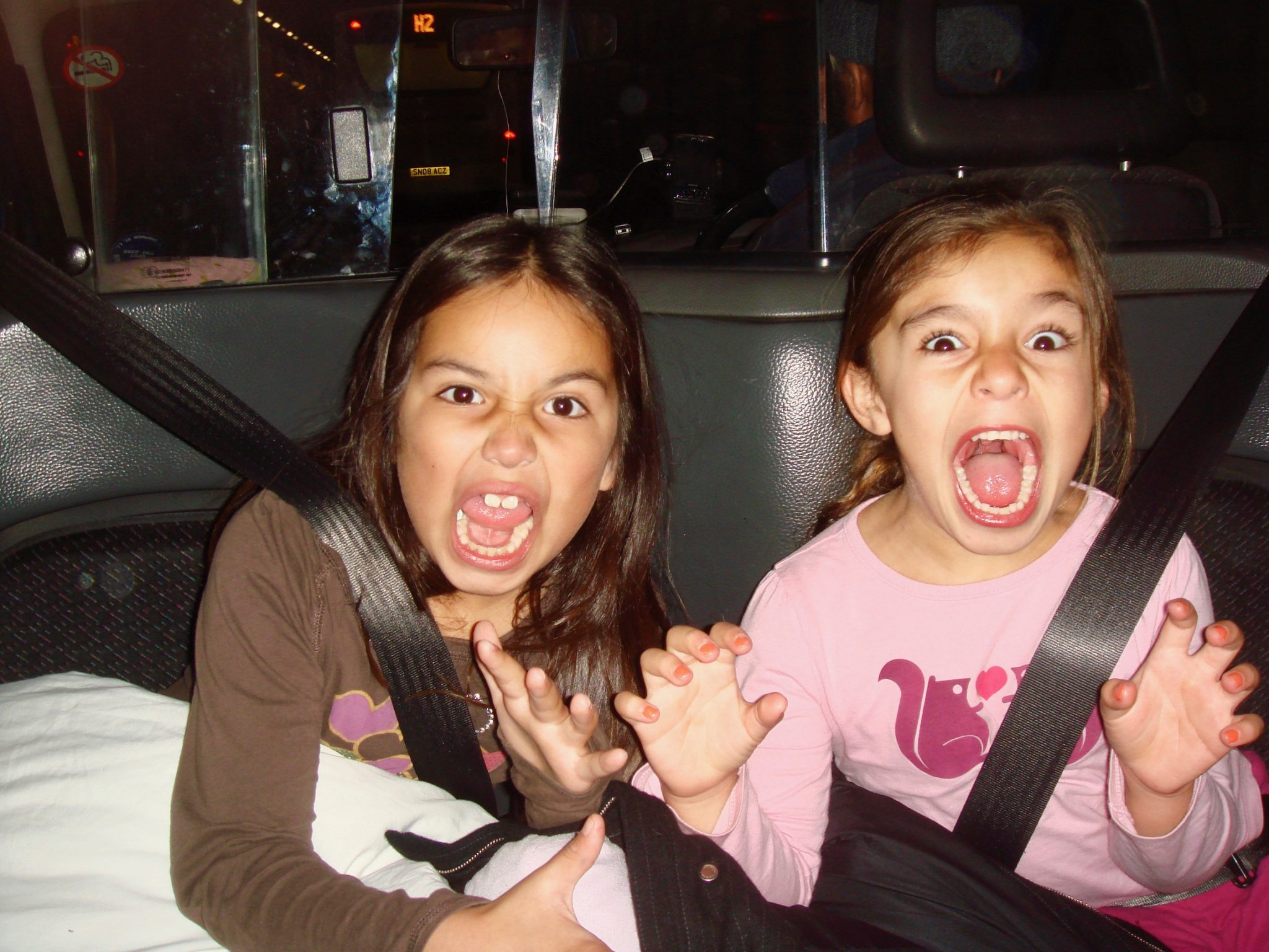 little girls making scary faces in London black cab