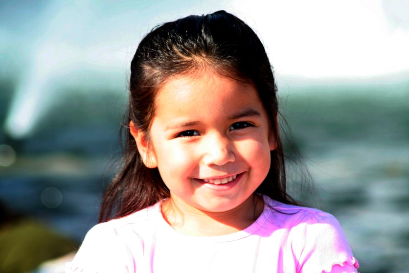 young Hispanic girl in park smiling at camera