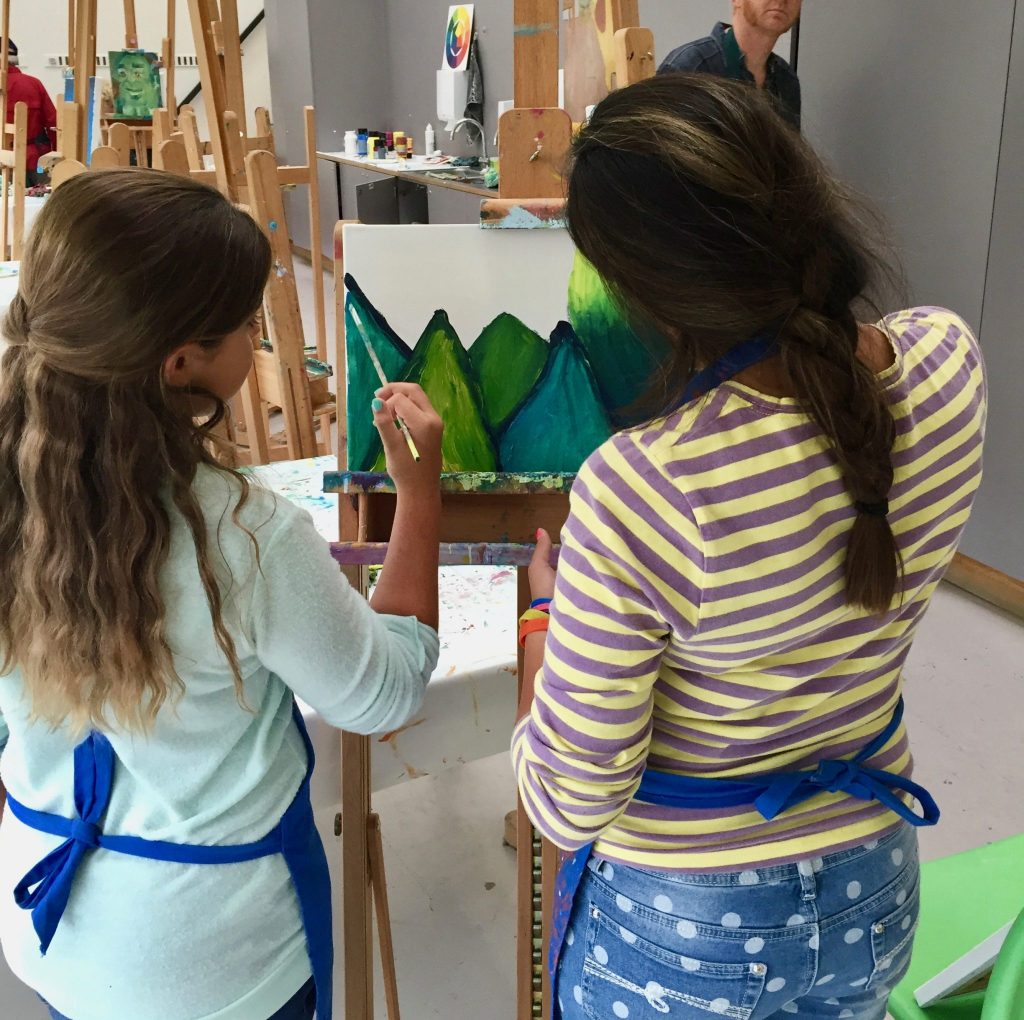two young girls creating a painting together at the Van Gogh Museum in Amsterdam