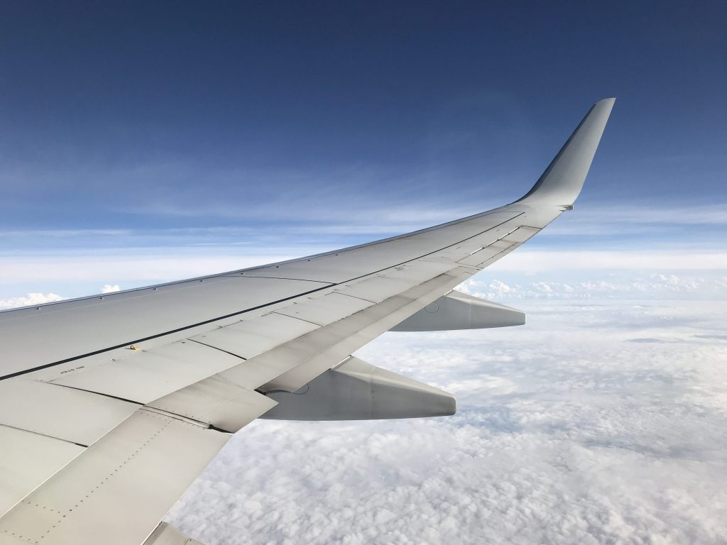 airplane wing flying over clouds with blue sky in the background