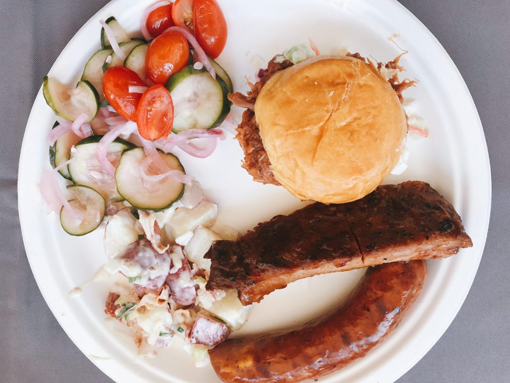 picnic lunch featuring Coleman Natural meats including ribs, sausages and pulled pork sandwich