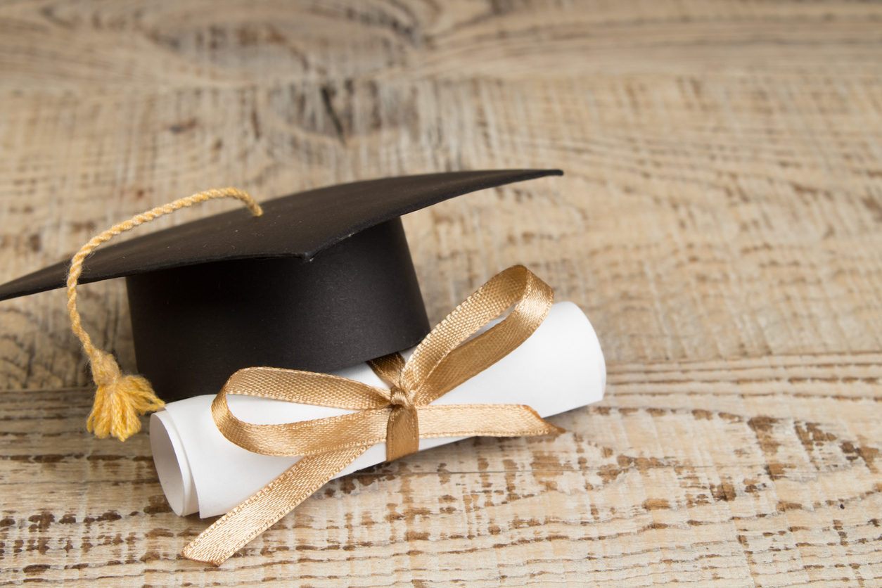 Graduation hat with gold tassel, scroll on the on a wooden table.