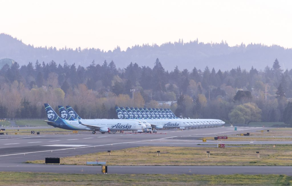 PORTLAND, OR / USA - April 7 2020: Grounded Alaska Airlines boeing 737s and airbus A320s parked next to one another on runway 3/21 at PDX Airport due to the significant drop in passengers.
