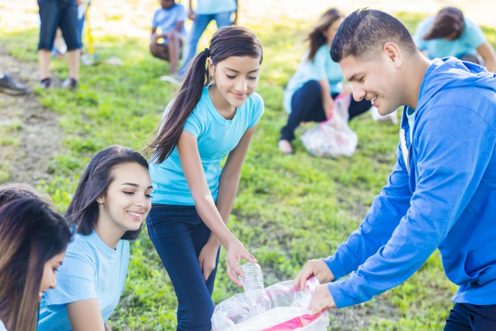 Happy Hispanic familly puts trash in a bag while cleaning up neighborhood park with their neighbors. The mid adult father holds a garbage bag as his preteen daughter puts a plastic bottle in the bag. They are wearing light blue shirts and the dad is wearing a bright blue hoodie. People are also pick up garbage behind them.